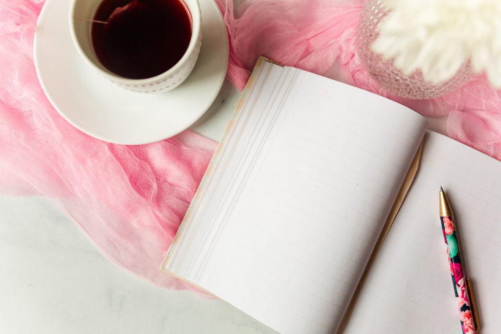 tea in mug, open notebook with pen