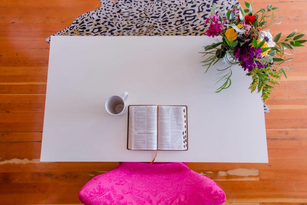 white desk, open bible, hot pink chair