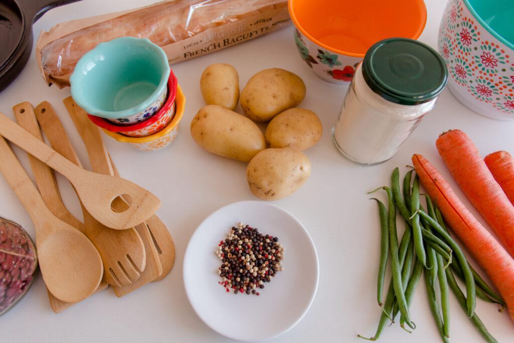meal prep ingredients: potatoes, green beans, carrots, peppercorns, flour, spatula