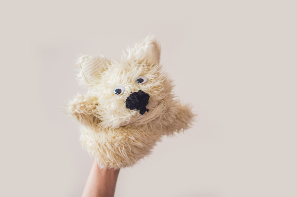 Puppet show dog on a gray background. Space for text or replicas.