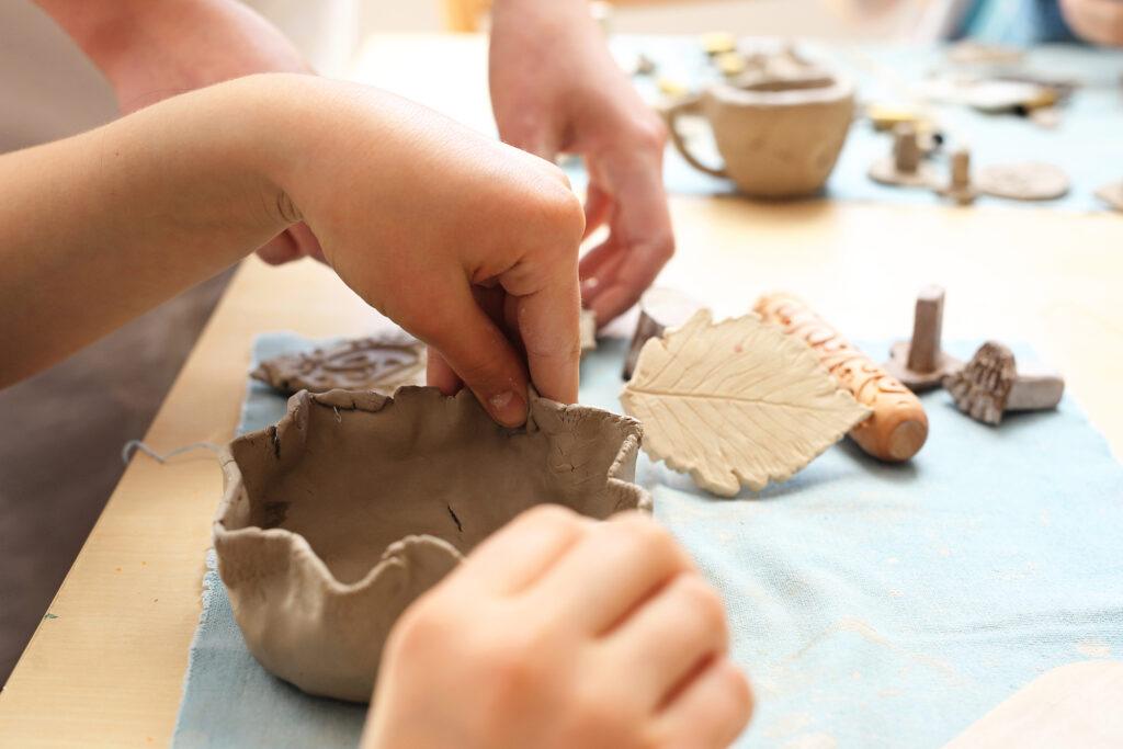 child's hand molding clay pot