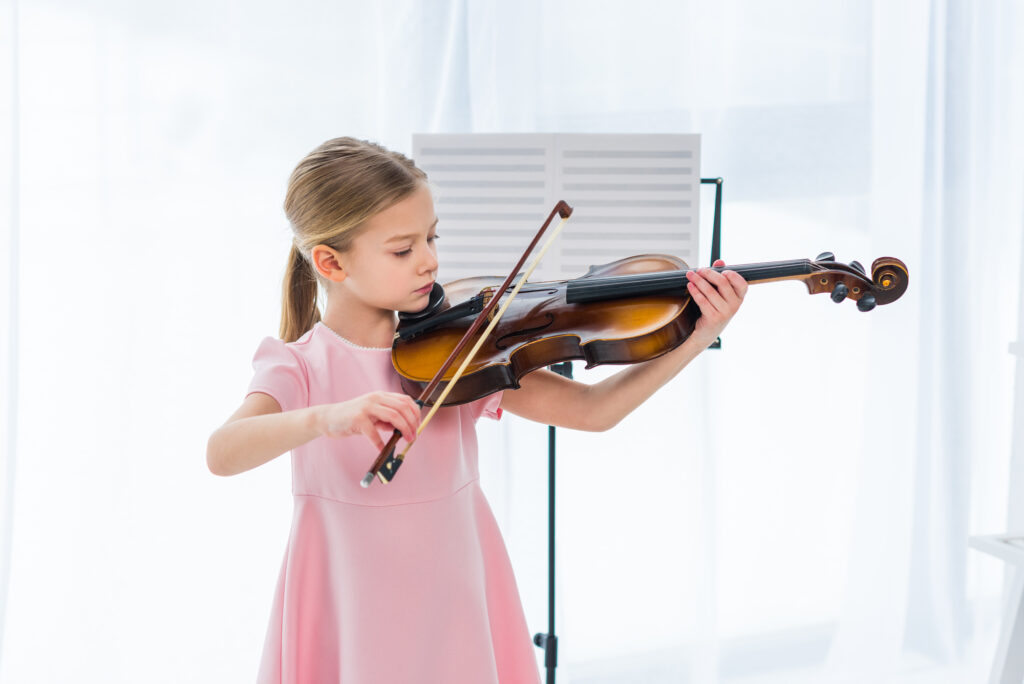 little girl in pink dress playing the violin