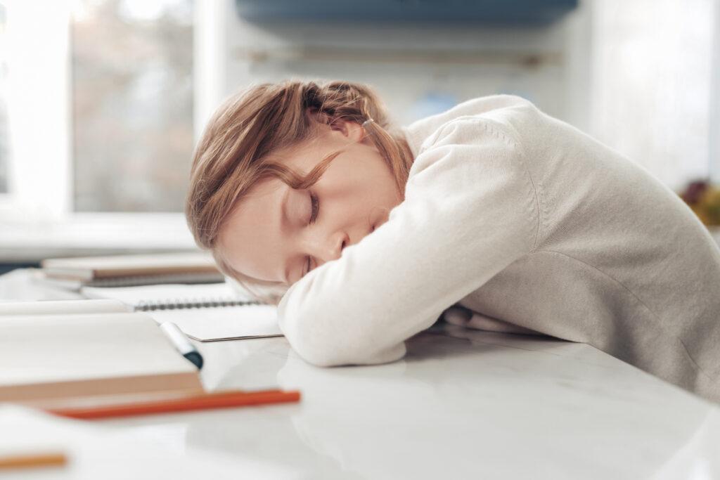 Tired little sleepy schoolgirl sleeping on workplace