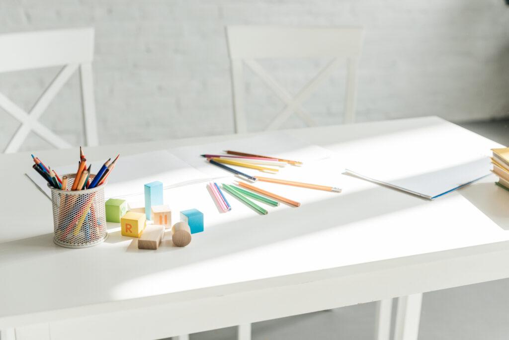 white school desk and pencils and blocks