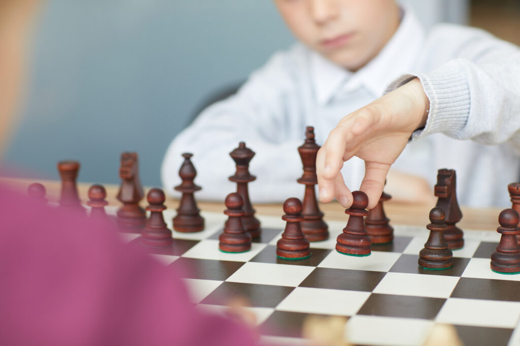 Schoolboy in white shirt making retaliatory move in chess game with girl in purple sweater