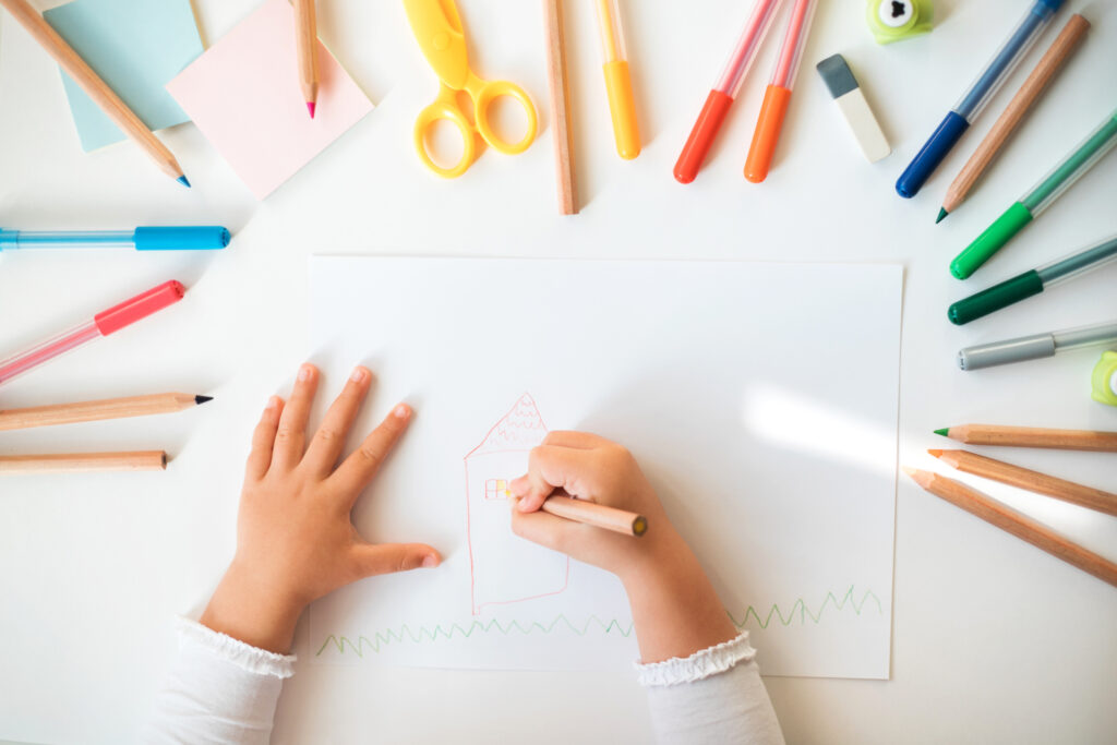 Close up of child's hands drawing at white paper.