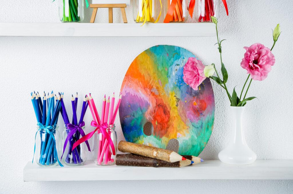 Bright pencils in glass jars on shelf