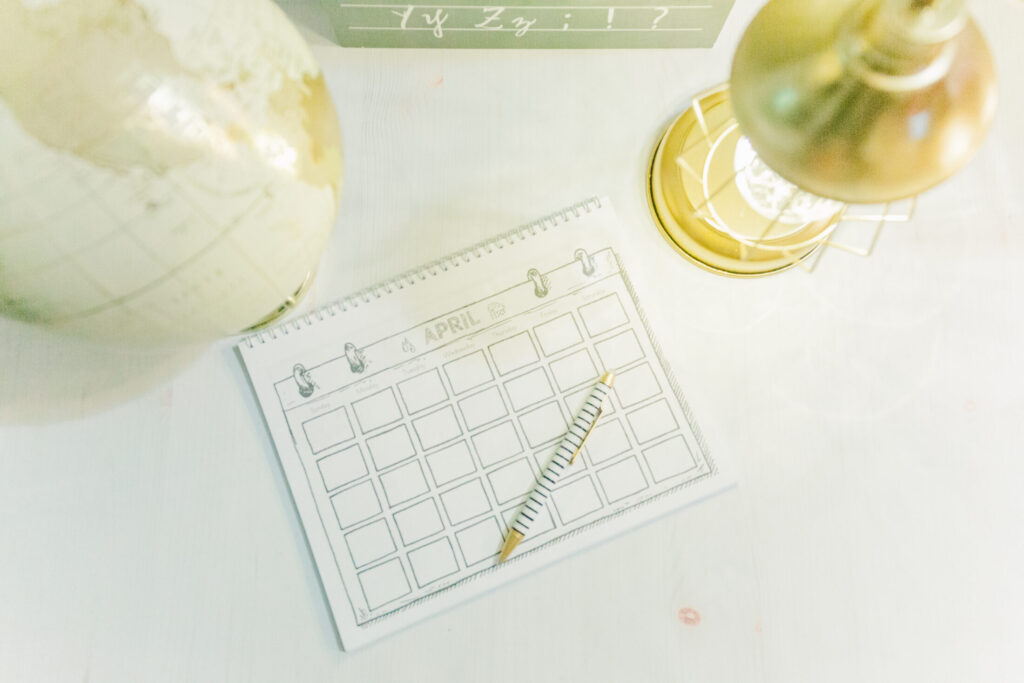 Weekly lesson planner, gold globe, table lamp on tabletop