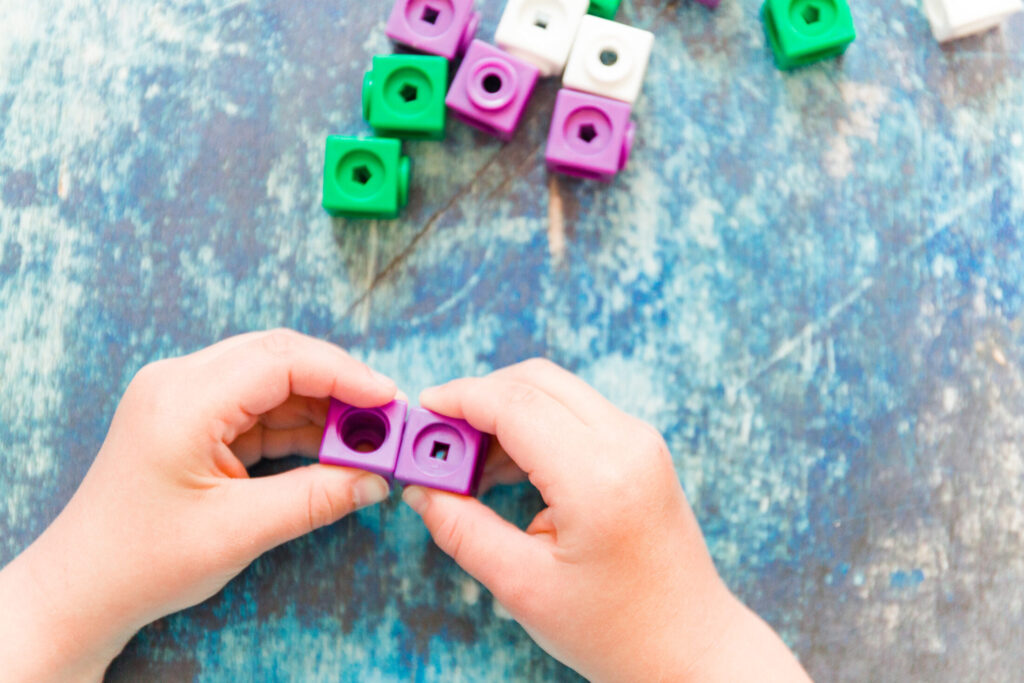 child's hands holding math manipulatives