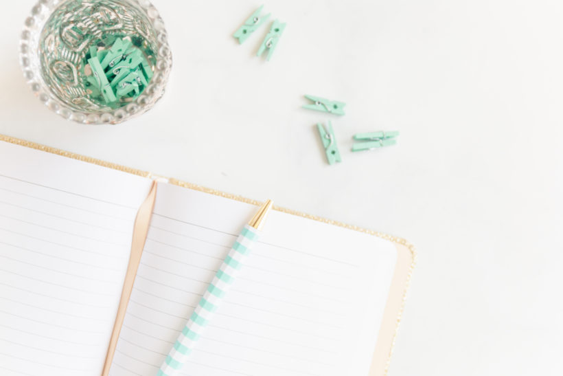 notebook with teal paper clips