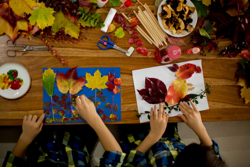 Children, applying leaves using glue, scissors, and paint, while doing arts and crafts in school, autumntime