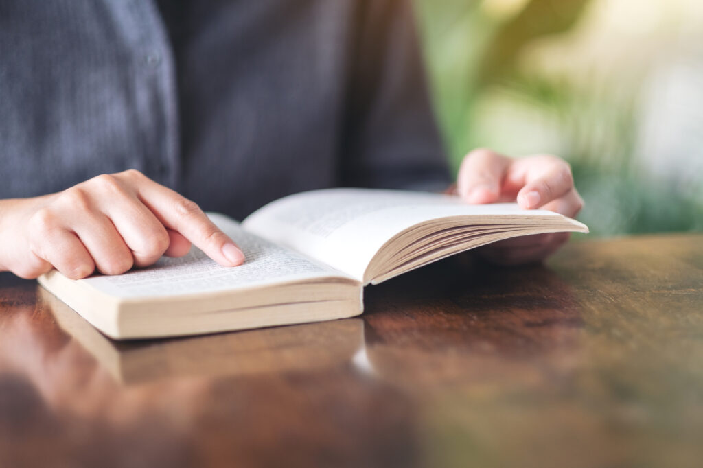 Closeup image of a woman pointing at a book while reading a vintage novel on wooden table