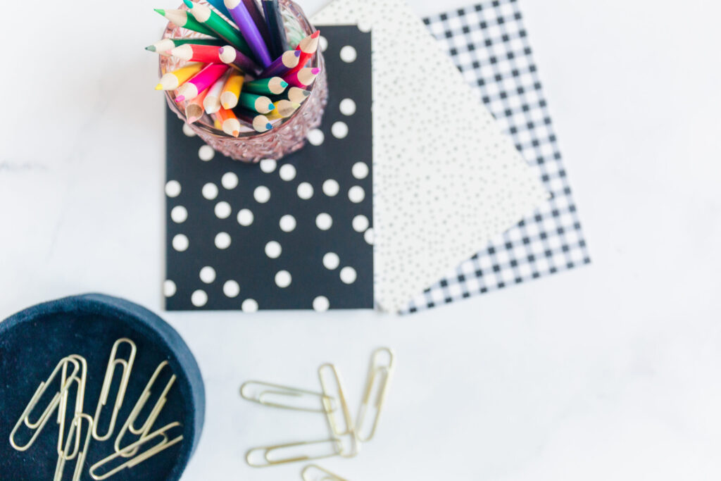 stationary with colored pencils in cup and gold paper clips