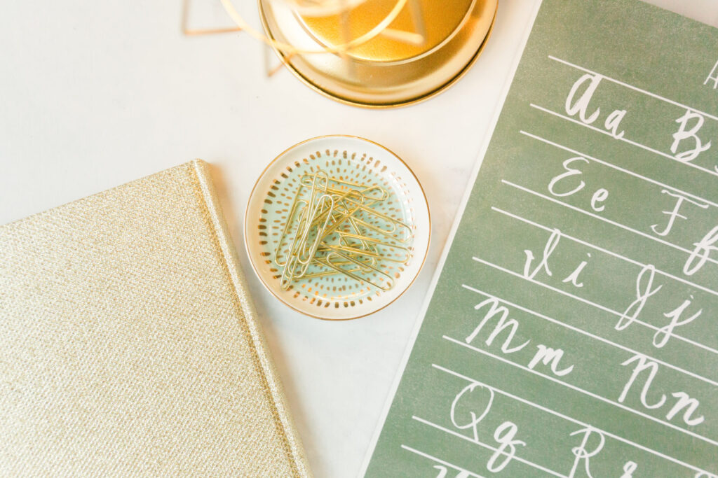 Alphabet Picture in Green, gold paper clips in tray and gold table lamp