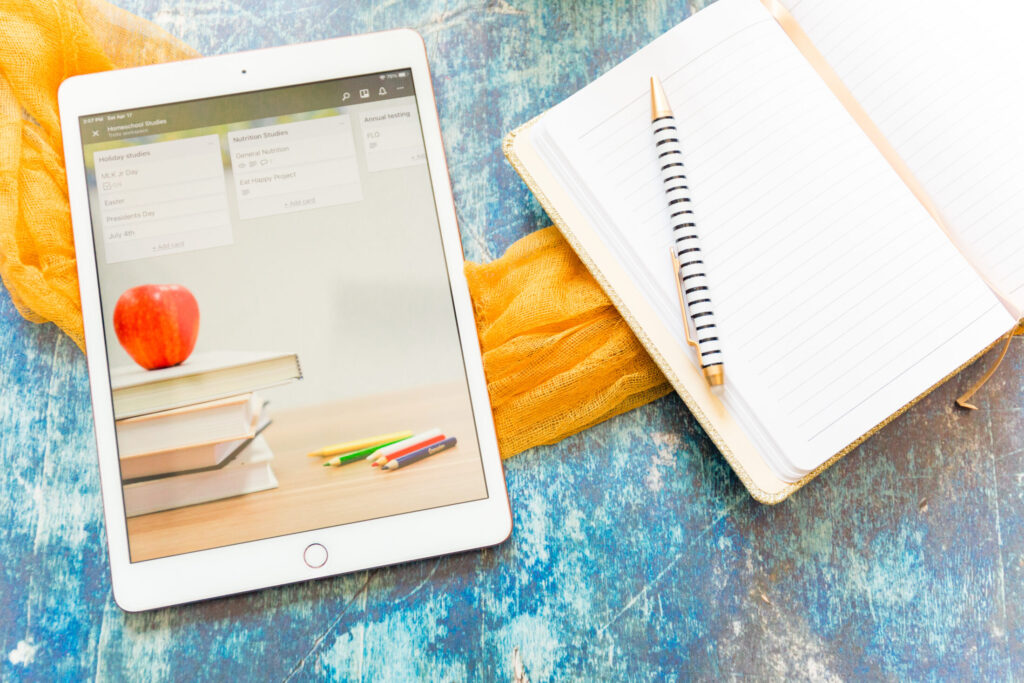 ipad with homeschool planner and notebook with pen